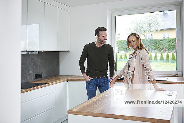 Couple examining kitchen in new flat