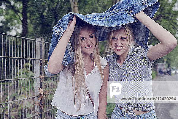 Two young women shletering from rain with a denim jacket