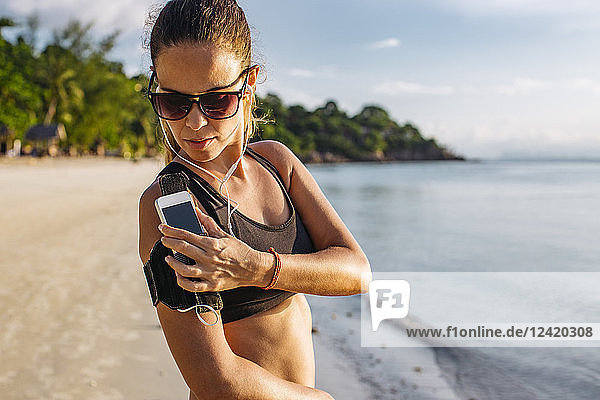 Thailand  Koh Phangan  Sportive woman during workout on the beach  smartphone