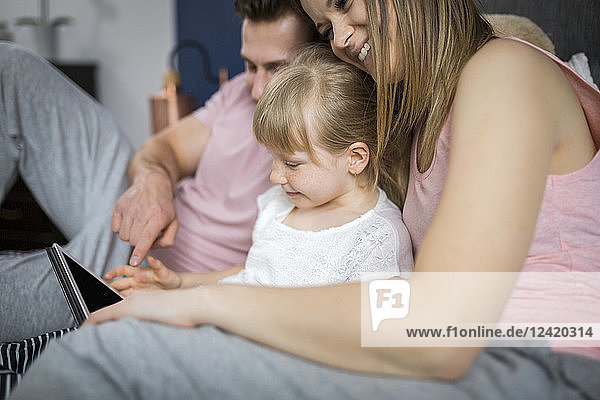 happy family sitting on bed  watching something on digital tablet with little daughter