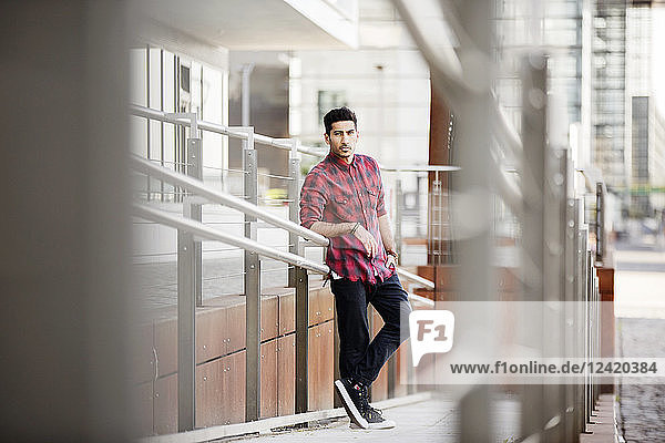Young man leaning on railing