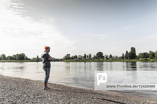 Mature man with red beanie enjoying Rhine riverbank