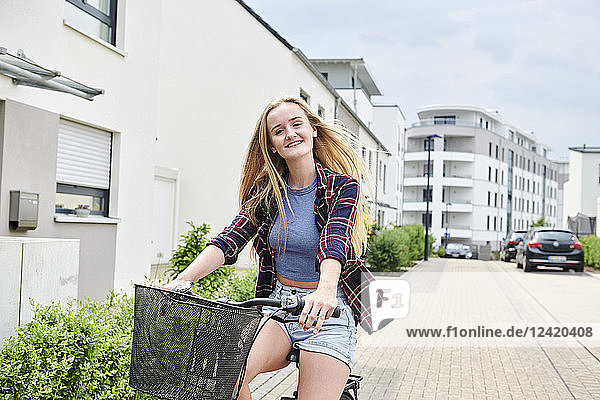Happy young woman riding bicycle in housing area