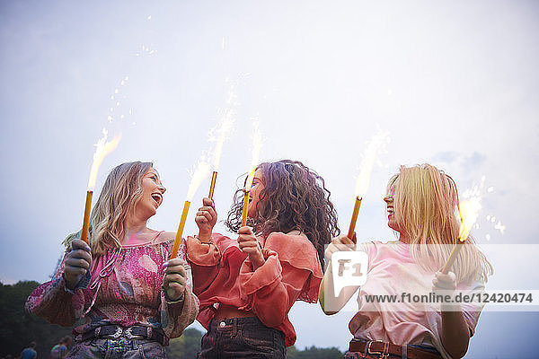Friends with sparklers dancing at music festival Friends with sparklers dancing at music festival