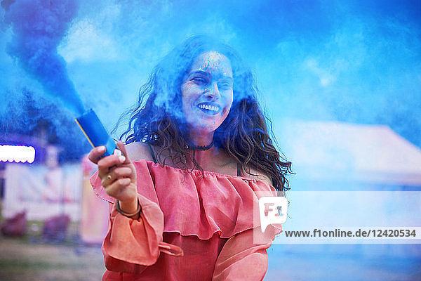 Happy woman holding smoke bomb at music festival Happy woman holding smoke bomb at music festival