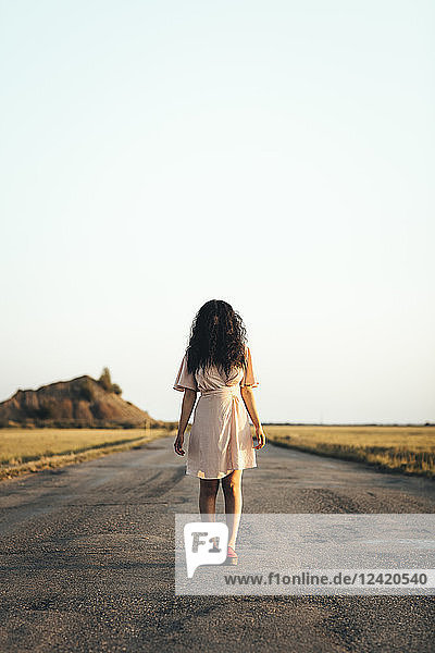 Young woman standing on country road  hiding face behind her brown hair