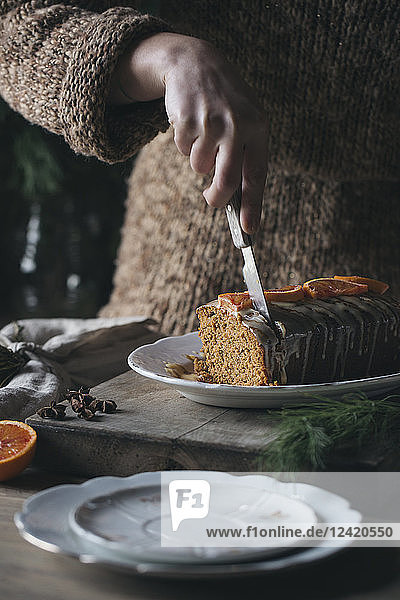 Woman's hand cutting home-baked Christmas cake  partial view