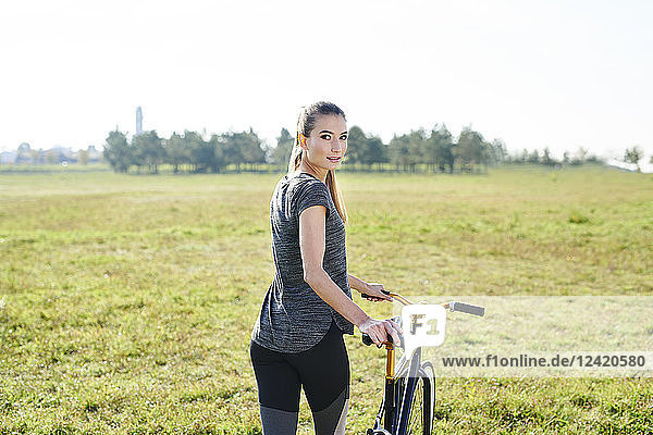 Sportive young woman with bicycle on a meadow
