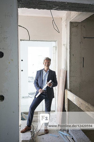 Portrait of smiling architect in building under construction