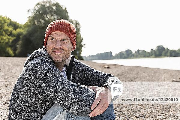 Mature man wearing red beanie sitting at Rhine riverbank
