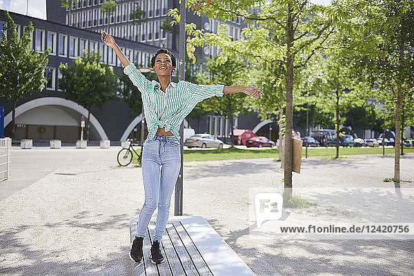 Happy young woman balancing on bench Happy young woman balancing on bench