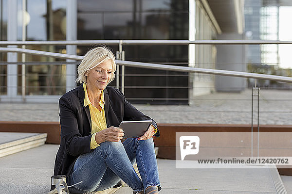 Smiling senior businesswoman sitting with tablet in the city
