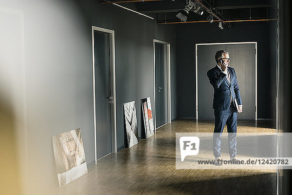 Mature businessman standing on office floor with paintings using cell phone