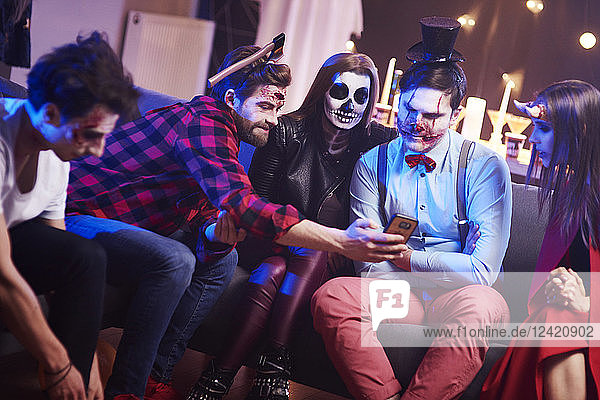 Friends using mobile phone at Halloween party