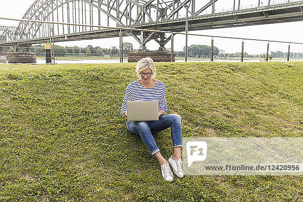Senior woman sitting on a dike using laptop