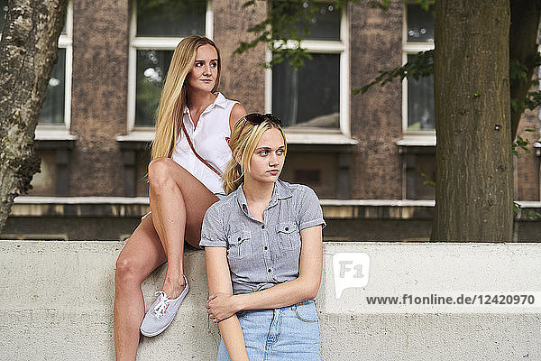 Two young women in the city looking sideways