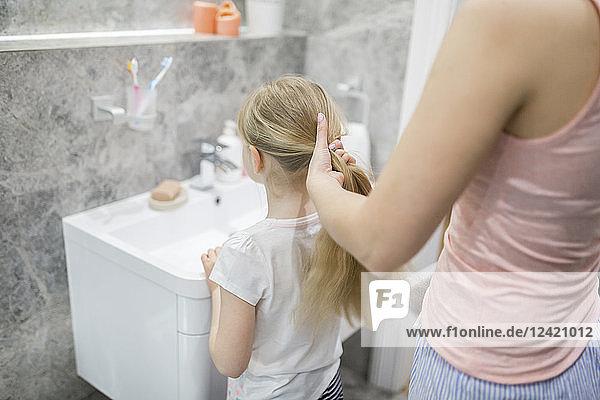 Mother combing daughter's hair in bathroom