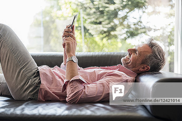 Smiling mature man lying on couch at home using a cell phone
