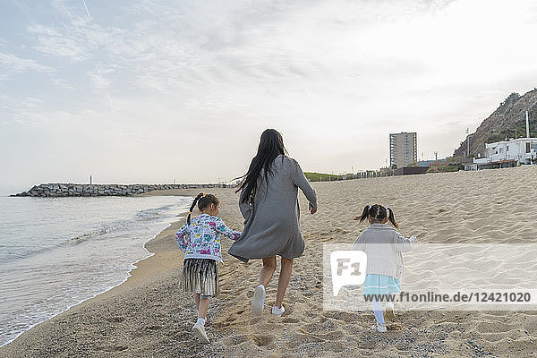 Mother with two daughters running on the beach