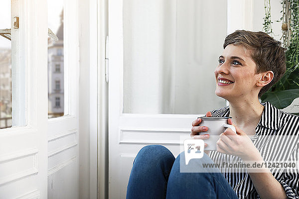 Happy woman sitting relaxed at window  drinking coffee