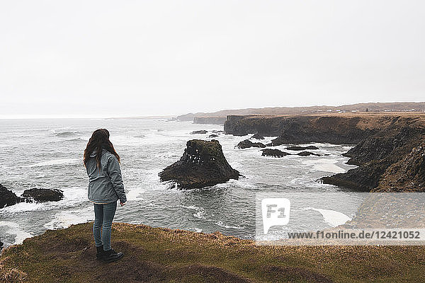 Iceland  back view of woman standing at coast