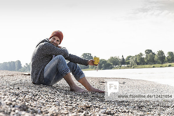 Mature man wearing red beanie and drinking coffee at Rhine riverbank