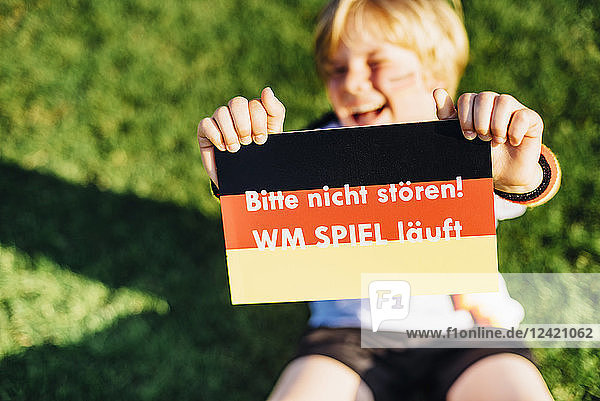 Boy showing do not disturb sign due to socce world championship