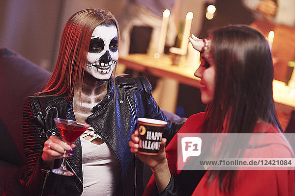 Women in creepy costume drinking at party Women in creepy costume drinking at party