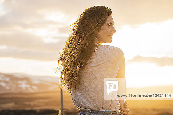 Iceland  young woman at sunset  rear view