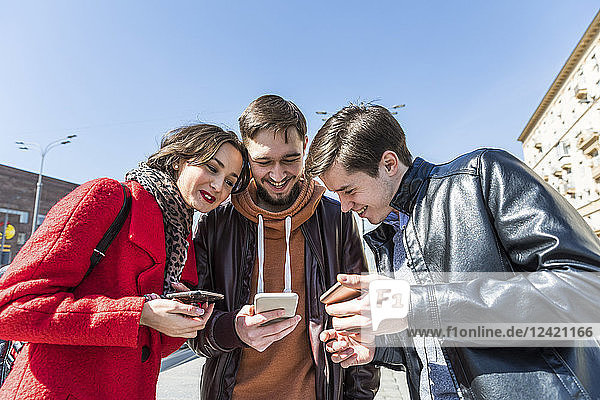 Russia  Moscow  three friends looking together at a smartphone