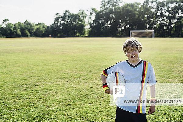 Boy wearing German soccer shirt  holding football