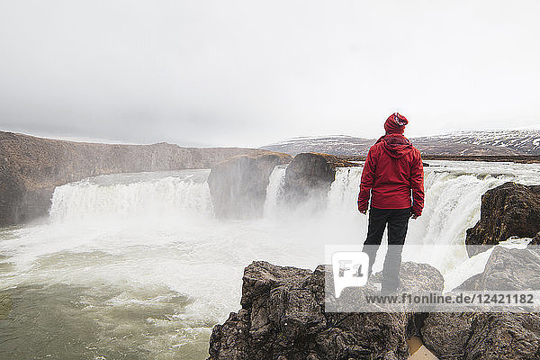 Iceland  man standing at Godafoss waterfall
