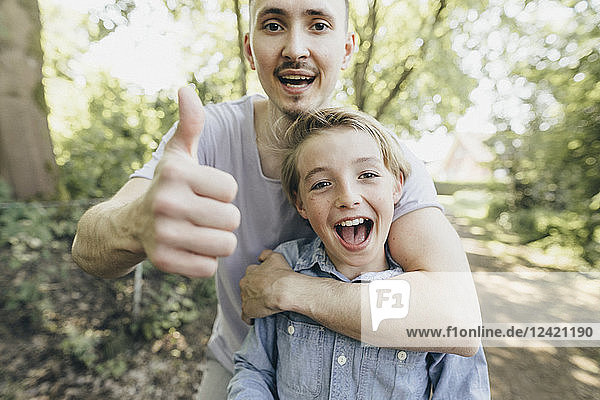 Portrait of happy young man embracing boy on forest path