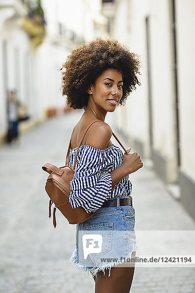 Portrait of fashionable young woman with small backpack on the street
