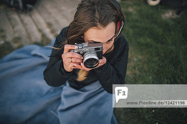 Young woman wrapped in a blanket taking a picture