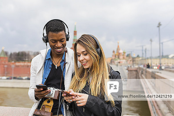 Russia  Moscow  multiracial best friends listening music with headphones