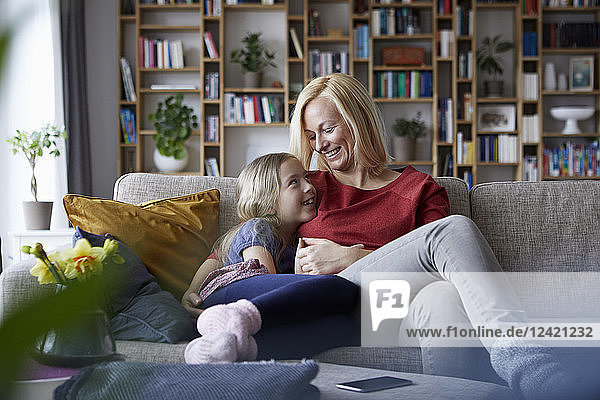 Mother and daughter cuddling on couch