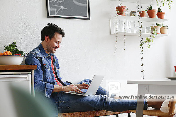 Man sitting at home  using laptop