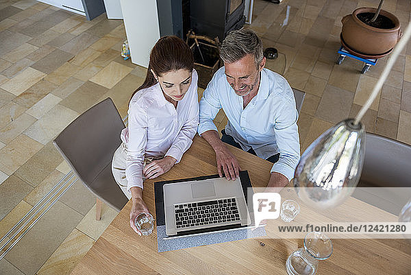 Couple sitting at table at home sharing a laptop