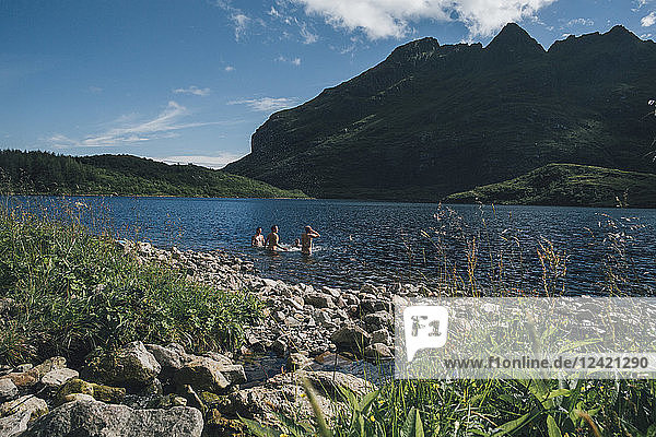 Norway  Lofoten  Moskenesoy  Three men bathing in Lake Agvatnet