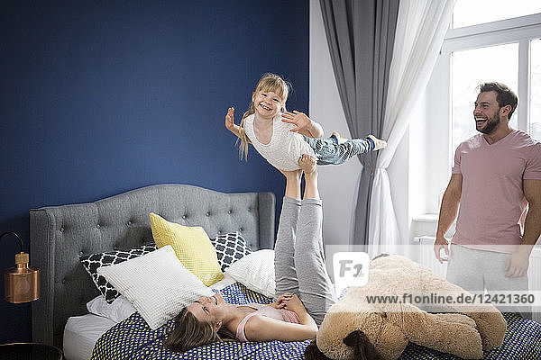 Family playing in bedroom  mother balancing daughter on her feet