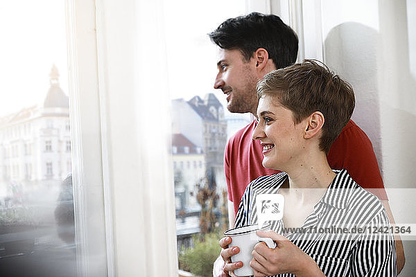 Relaxed couple standing at the window  woman drinking coffee