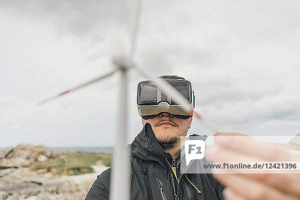 France  Brittany  Meneham  man with miniature wind turbine wearing VR glasses at the coast