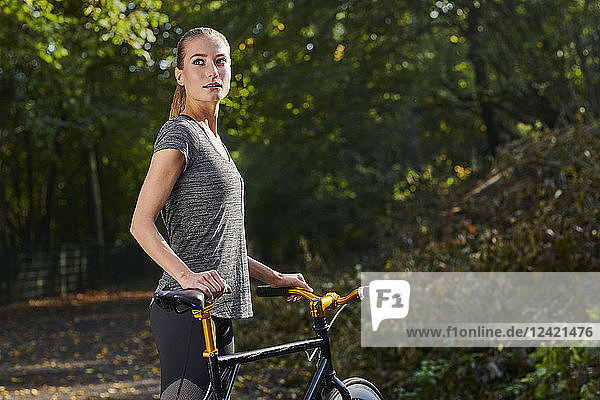 Portrait of sportive young woman with bicycle in a forest