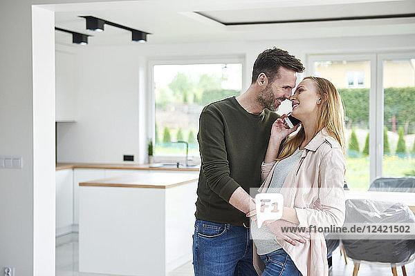 Man kissing pregnant woman in empty flat Man kissing pregnant woman in empty flat