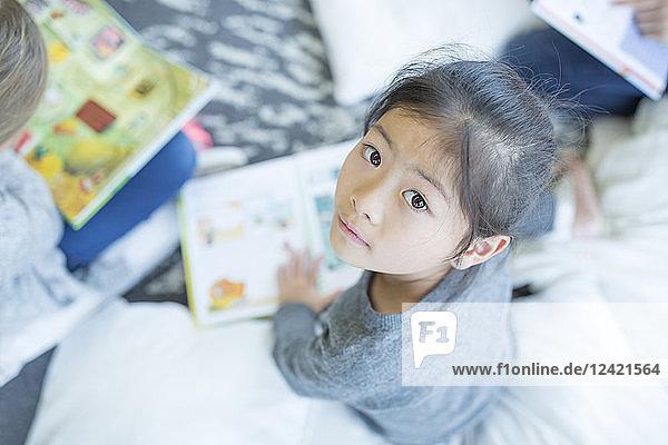 Portrait of schoolgirl sitting on the floor with book in school
