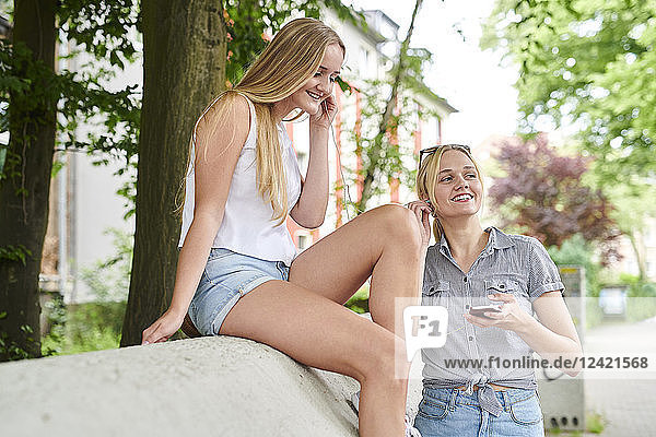 Two young women sharing cell phone and earphones outdoors