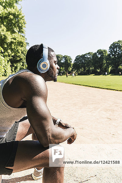 Smiling young athlete taking a break  wearing headphones  listening music