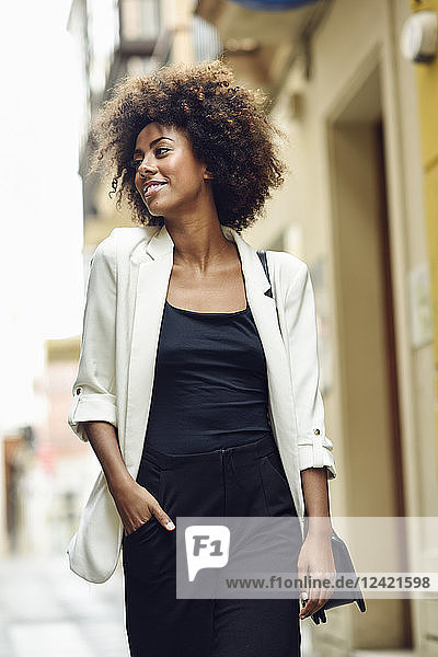 Portrait of fashionable young woman with curly hair in the city
