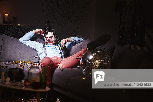 Man in Halloween costume sleeping on couch after party Man in Halloween costume sleeping on couch after party